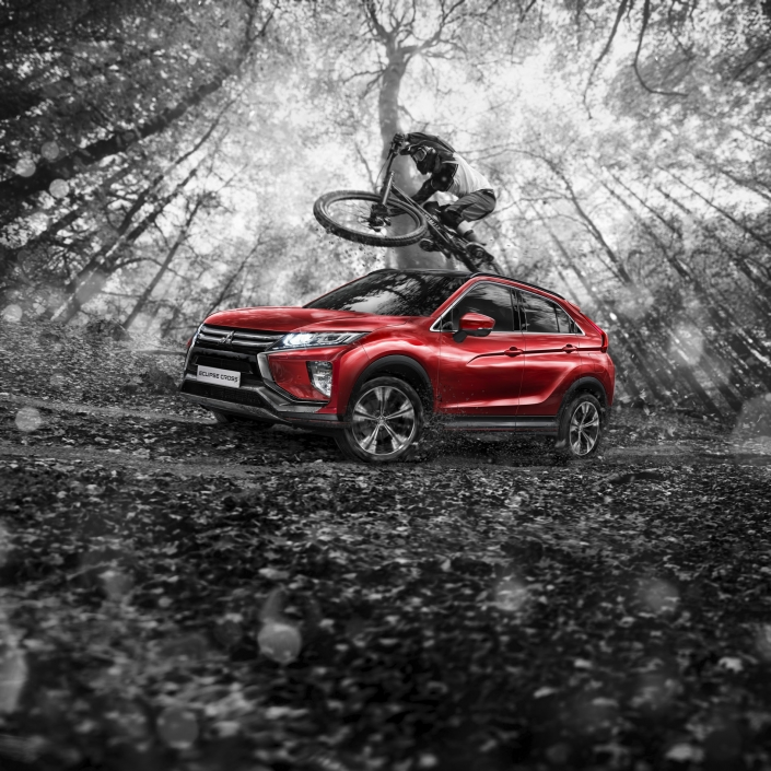 mitsubishi eclipse cross red car driving through forest, mountainbiker jumping composing by tobias winkler bildbearbeitung muenchen